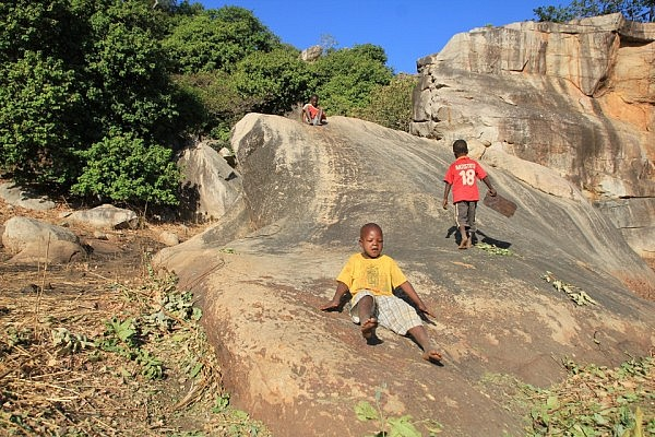 Children sliding down a boulder